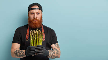 Indoor shot of male chef holds spring vegetable, asparagus for preparing delicious salad, thinks which dish to cook, suggests healthy eating, has long ginger beard, wears black cap and t shirt