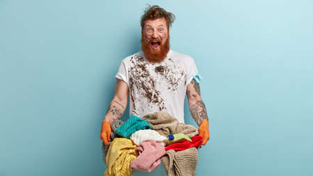 Photo of annoyed redhead man shouts desperately angrily, being dirty, cries from despair, has deadline for washing, carries basin with laundry, isolated over blue background. Housework concept
