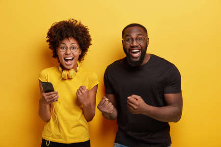 Overjoyed millennial dark skinned woman and man dance and clench fists from joy, listen music on cell phone, enjoy favourite playlist have fun together, use modern headphones, isolated over yellow Banque d'images