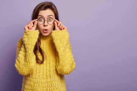 Emotive surprised student cann not believe she failed exam, touches rim of glasses, keeps lips rounded, wears yellow sweater, expresses shock and wonder, isolated over purple wall, free space