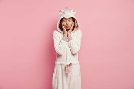 Shot of pleasant looking woman makes grimace, keeps hands on cheeks, pouts lips, has bugged eyes, dressed in warm unicorn costume, models againt pink background. Funny girl foolishes before sleep