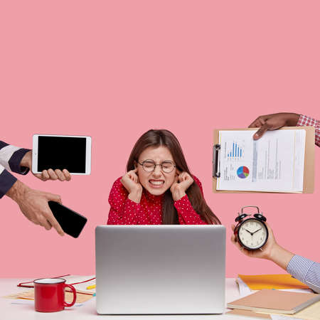 Vertical shot of dissatisfied woman works in office, covers ears, ignores reproaches of colleagues who bother her on different questions, works on modern laptop computer, isolated on pink background
