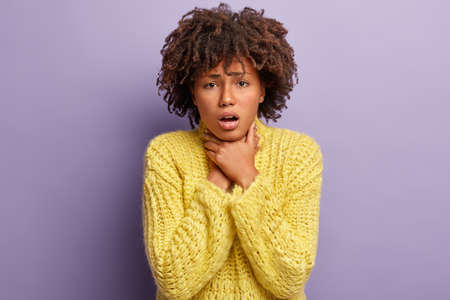 Asphyxiate and health problems concept. Desperate dark skinned woman has painful strangle in throat, suffers from suffocation, wears yellow jumper, demonstrates suicide gesture, isolated on purple Archivio Fotografico