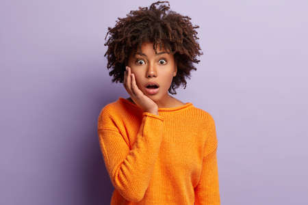 Facial expressions concept. Stupefied attractive woman keeps jaw dropped, touches cheek, hears astonishing news, can not believe rumors, wears casual orange knitted jumper, isolated over purple wall