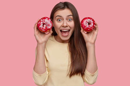 Photo of attractive joyful woman carries two delicious doughnuts, opens mouth widely, has long hair, pleased to eat tasty dessert, dressed in casual outfit, isolated over pink background. People, food