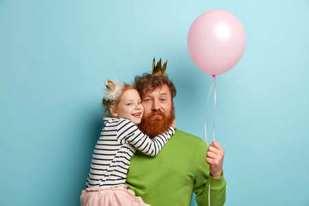 Fancy party concept. Lovely cheerful little kid embraces affectionately father who looks tired of amusing children, holds pink balloon, have funny time together, wear festive crowns, isoaled on blue