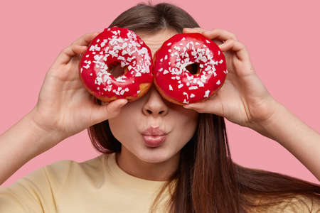 Close up of pretty woman covers eyes with donuts, has healthy skin, enjoys sweet dessert, has dark long hair, poses over pink studio wall. Beautiful female eats doughnuts keeps to diet. Sweet dish