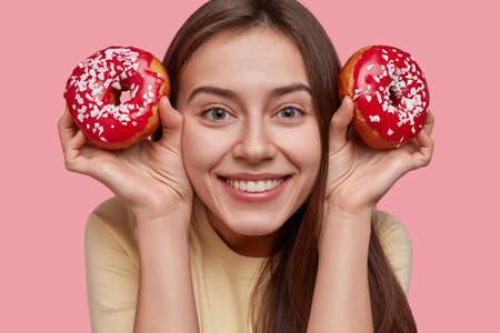 Headshot of pretty young European lady has satisfied expression, shows white teeth, holds delicious doughnuts, being in high spirit, isolated over pink background. Teenager enjoys sweet dessert Stok Fotoğraf