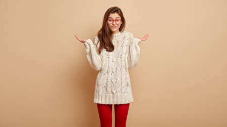 Half length shot of confused woman spreads hands, feels doubt what to do, asks why its problem, wears white jumper and red tights, gestures over beige background, says I dont know. Puzzled situation