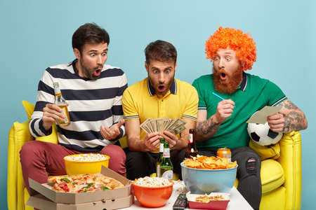 Stupefied men look surprisingly at cash, excited to win bet, watch football game on television, involved in gambling, eats fast food. Emotional guy with lots of money, enjoy league of champions