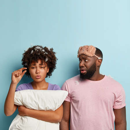 Vertical shot of dissatisfied female demonstrates small hand gesture, says she had little sleep, asks time for rest, nervous husband in casual t shirt and eyemask looks at wife. Bed time concept