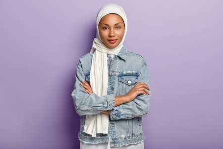 Attractive Eastern woman covers head with white headscarf to guard her dignity and power, has special dress code, keeps hands crossed, looks with modesty, poses over purple background. Islamic rules Reklamní fotografie