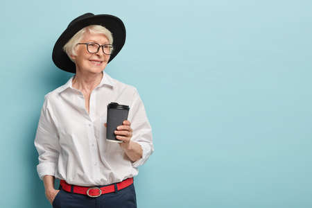 Portrait of happy elderly woman being on pension, has meeting with former colleagues, holds takeaway coffee, wears stylish white shirt, trouses with red belt, keeps hand in pocket. Leisure, retirement