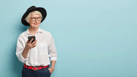 Half legth shot of stylish elderly female pensioner uses smartphone easily, being always in touch, sends text messages to daughter, looks happily aside, isolated on blue wall. People, age, technology
