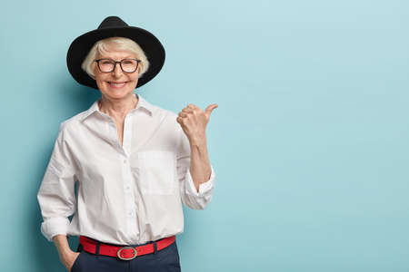 Waist up shot of friendly looking senior lady in stylish headgear, white elegant shirt and formal trousers, holds hand in pocket, points thumb away, has happy smile, advertises something nice