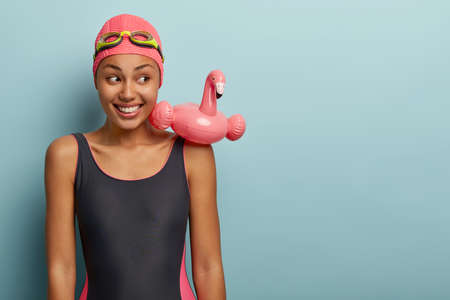 Sporty slim female with dark skin wears bathing suit, has swimming ring in shape of pink flamingo, goggles on head, spends free time in contemporary leisure center, ready for swim. Active rest Stock Photo