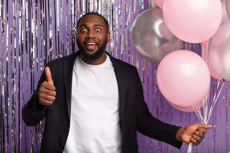 Positive dark skinned guy gives thump up at camera, likes brilliant idea of organizing party, holds bunch of air balloons, has widely opened eyes, celebrates special occasion, violet tinsel curatin