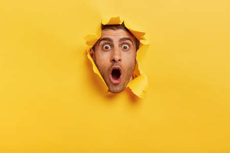 Stupefied young man with bristle keeps jaw dropped from surprisement, has popped eyes, stares through yellow torn paper, impressed by shocking rumors. People, human emotions and reaction concept Reklamní fotografie
