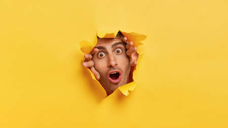 Stupefied dark eyed European man tears yellow paper, stares through hall with scared expression, notices something terrified, has widely opened eyes and mouth. Yellow background. Omg concept Imagens