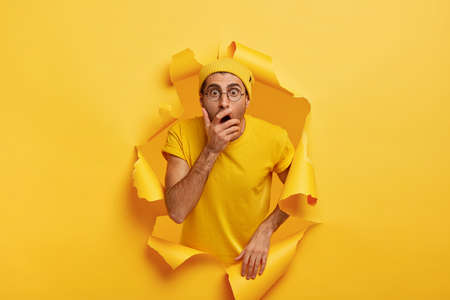 Photo of surprised scared man breaks through color paper wall, covers mouth, has stupefied expression, can not believe his eyes, wears stylish headgear, eyewear and t shirt in one tone with background