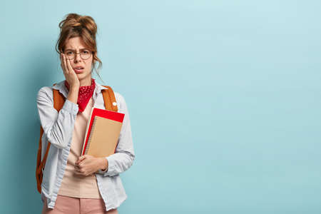Discontent unhappy student fails exam, upset to receive bad mark, keeps hand on cheek, holds notepads, has problems with studying, worries about result, poses with bag over blue studio background
