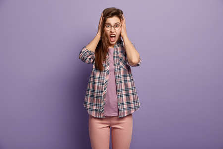 Hysteric annoyed young female covers ears with hanfds, doesnt want to hear complaining, screams angrily, wears round glasses, checkered shirt, pink trousers, isolated over purple background.