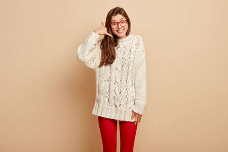 Call me back. Smiling attractive young woman gestures and says dont forget to call, wears long white sweater and red tights, stands over beige background. Body language and communication concept