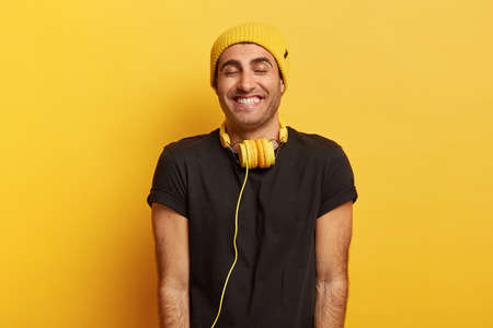 Handsome positive man with headphones on neck, smiles broadly and closes eyes from pleasure, wears hat and black t shirt, enjoys nice sound, listens wonderful songs, isolated on yellow bakground.