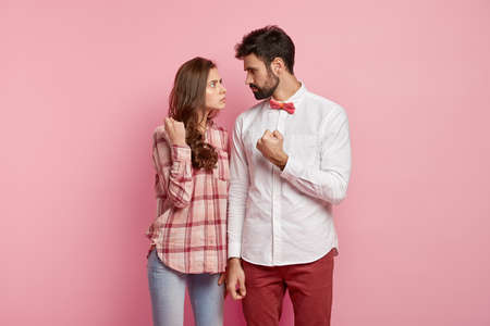 Angry husband and wife look strict at each other, show fists, have quarrel, dressed in stylish outfit, sort out relationships, decide about house duties, gesture angrily, stand against pink background Foto de archivo