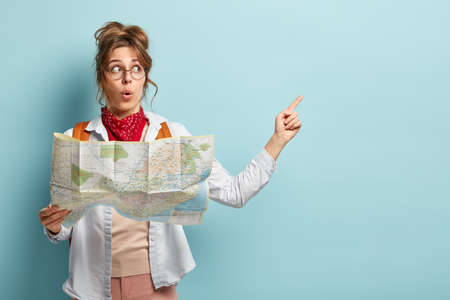 Shocked impressed female tourist points at copy space, holds travel map, searches right route during trip, surprised to be lost in unknown place, isolated on blue wall. Traveling and tourism concept
