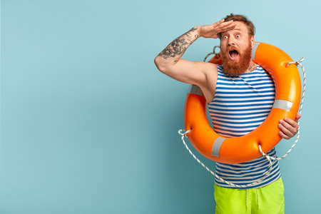 Surprised young holiday maker with red hair and beard, comes on beach with safety equipment as cannot swim, keeps hand on forehead, focused into distance, shocked to see drowning man in sea. Reklamní fotografie