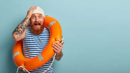 Stressed frightened life saver in panic, faces troublesome situation on beach, yells from fear, cannot manage by himself, carries orange lifebuoy, holds hand on hand, screams and demands help
