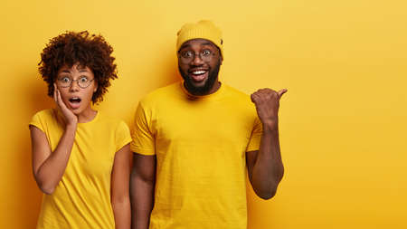 Studio shot of surprised woman with bated breath, stands closely to dark skinned guy who points aside on blank space, see something awesome, wear casual yellow t shirts, express shock and joy