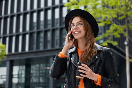 Joyful European woman with happy facial expression, has telephone conversation in roaming, drinks coffee to go, poses against modern constructed building, arranges meeting, dressed in stylish clothes