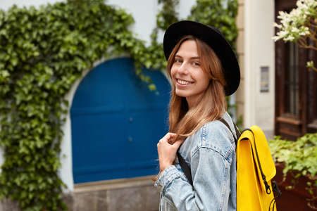 Sideways shot of cheerful lovely female strolls across old street with green vegetation, wears fashionable hat and denim jacket, carries little yellow rucksack, smiles at camera, enjoys weekend Standard-Bild