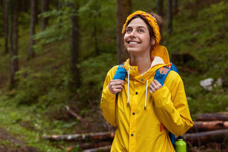 Happy European woman with delighted expression, looks upwards, being in good mood, breathes fresh forest air, wears yellow rain coat, wanders outdoor in green wood, enjoys nature. Copy space aside