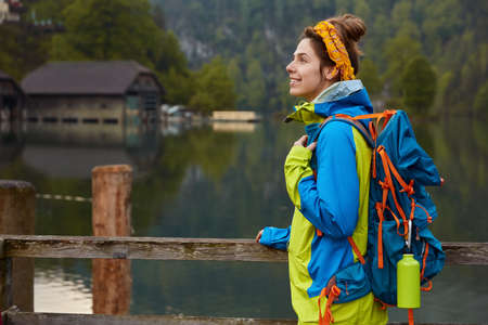 Sideways shot of cheerful woman traveler stands on wooden bridge near river or lake with small house into distance, breathes fresh air, enjoys nature, wears anorak, carries rucksack, has journey
