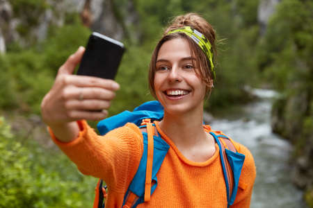 Cheerful smiling young female traveler makes photo of herself, uses modern cell phone, wears casual orange jumper, breathes fresh air in forest near river. People, technology, wanderlust concept Banco de Imagens