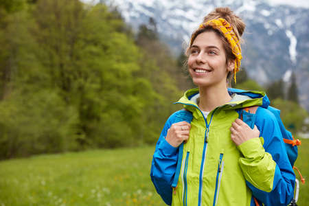 Horizontal shot of happy carefree young woman strolls outside against mountain landscape, enjoys spending free time on meadow, wears anorak, yellow headband, being in good mood. Leisure concept Stockfoto
