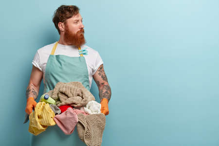 Red haired young man overstained with housekeeping, holds basin with pile of laundry, wears casual t shirt and apron, looks away, isolated over blue background, has thoughtful look, focused away Standard-Bild