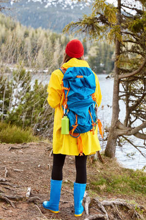 Female tourist stands back to camera, dressed in casual yellow raincoat, rubber boots, breathes fresh air near mountain lake, leads active lifestyle, has trip. People, traveling, nature concept Banco de Imagens
