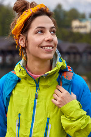 Vertical shot of positive Caucasian woman looks away, strolls and breathes fresh air, wears yellow headband and anorak, wears rucksack with packed things, enjoys freedom. Time for active rest Banco de Imagens