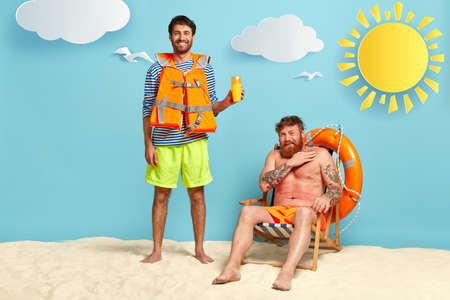 Photo of glad man suggests friend using sunscreen, has positive smile, wears lifejacket, upset red haired guy has sunburnt skin, sits at deckchair, needs sunblock lotion. Skincare and summer vacation