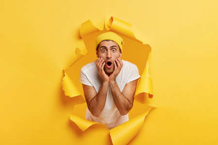 Stupefied young European man feels confused and amazed, panicks and looks surprised, keeps mouth widely opened, wears yellow hat and white t shirt, stands in torn hole over yellow background Stock fotó