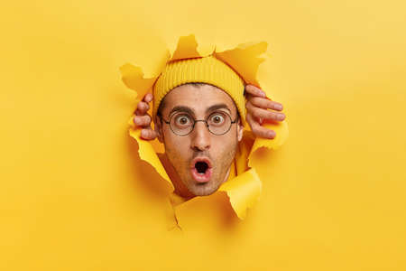 Terrified young man has shocked facial expression as someone out blame on him, stands speechless, keeps head in hole of torn yellow wall, wears hat and spectacles. Male head in ripped paper.