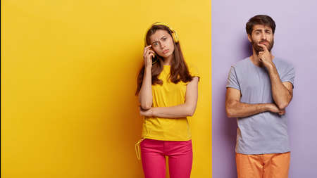 European couple dont speak to each other after quarrel, woman ignores husband listening music in headphones, pensive serious guy holds chin, contemplates about something. Two colored background Banco de Imagens