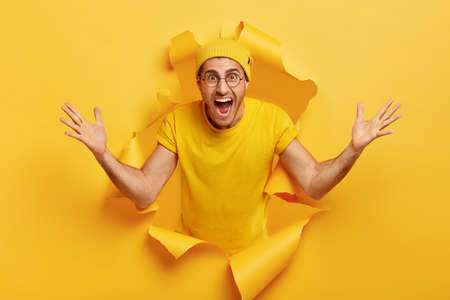 Happy emotional Caucasian man shows huge gesture, measures something big, shouts loudly, wears yellow headgear and t shirt, poses in torn paper wall. People and size concept. Monochrome shot Stock Photo