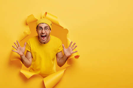 Emotional unshaven guy stands in ripped paper hole of yellow background, yells loudly, gestures and shows palms, tries to prevent you from danger, shouts be carefully, wears bright hat and t shirt