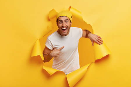 Happy young man points at himself, expresses wonder he was chosen, smiles broadly, wears casual clothes, poses in ripped paper hole, isolated over yellow background, being mentioned or picked