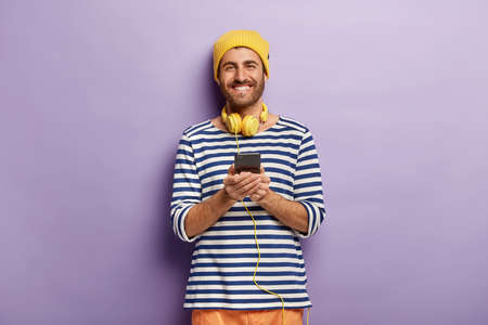 Waist up shof of glad attractive hipster wears stereo headphones and holds modern cell phone, listens audio track and checks notification, dressed in striped sailor jumper, yellow headgear, smiles